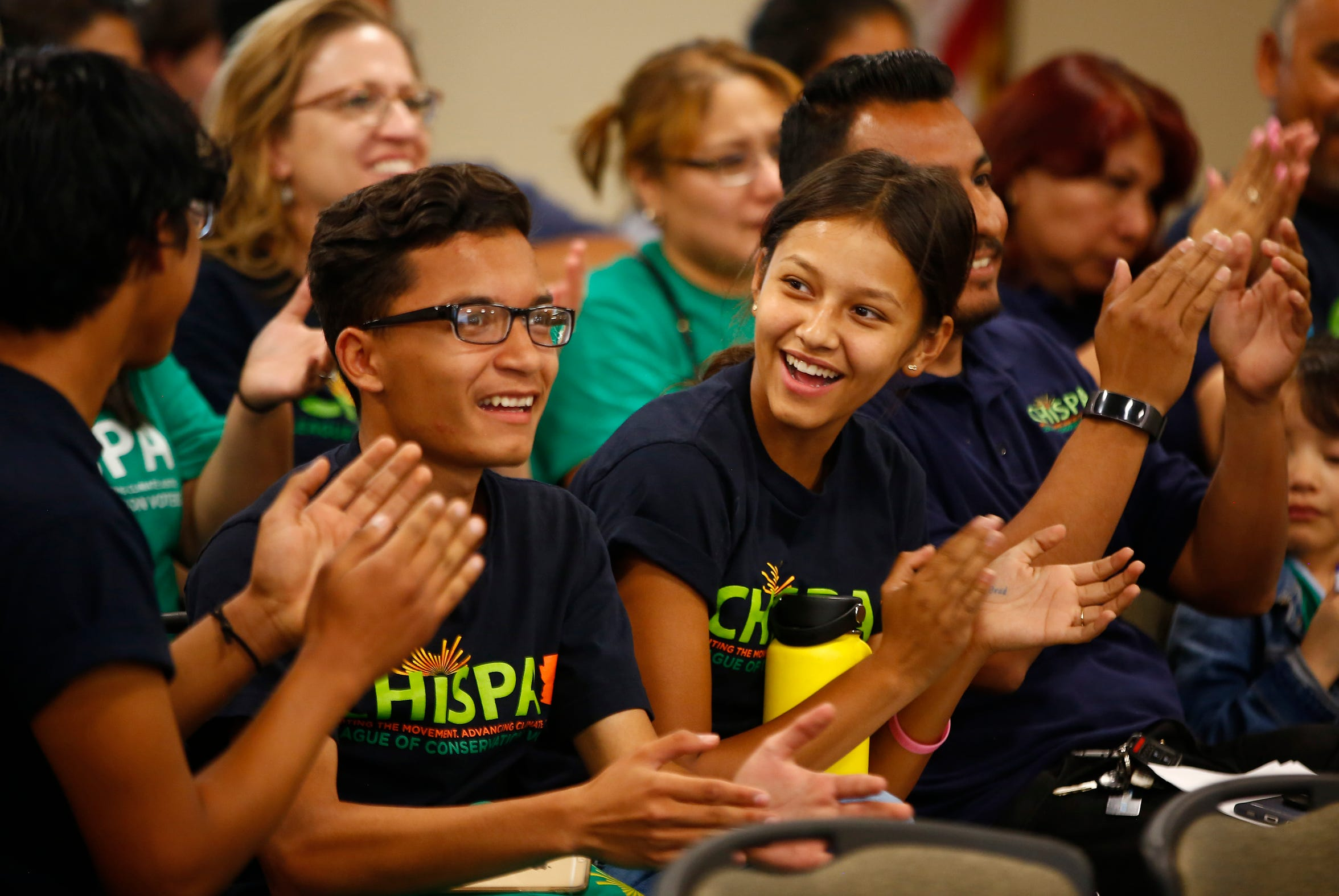 From left to right: Erik Gomez, Levin Escarcega and Monica Aceves clap with their coach Julio Zuniga as the board approves an electric school bus during a Phoenix Union High School District governing board meeting in Phoenix on April 11, 2019.