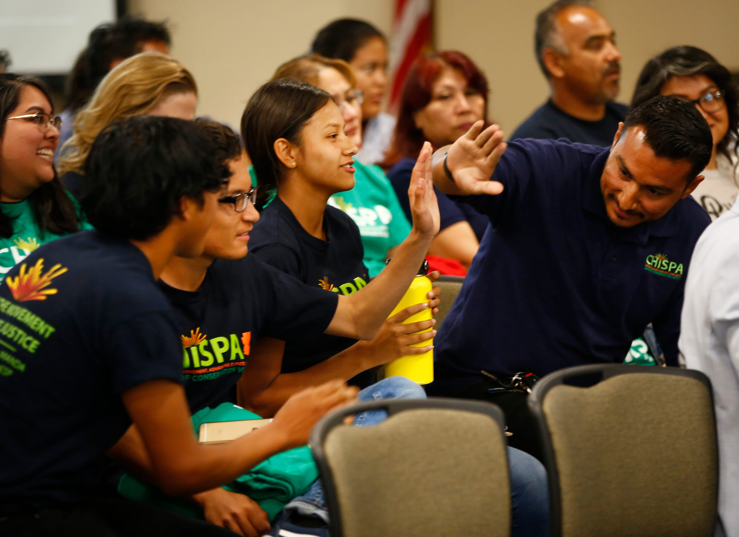Levin Escarcega (left) high-fives coach Julio Zuniga as the board approves an electric school bus during a Phoenix Union High School District governing board meeting in Phoenix on April 11, 2019.
