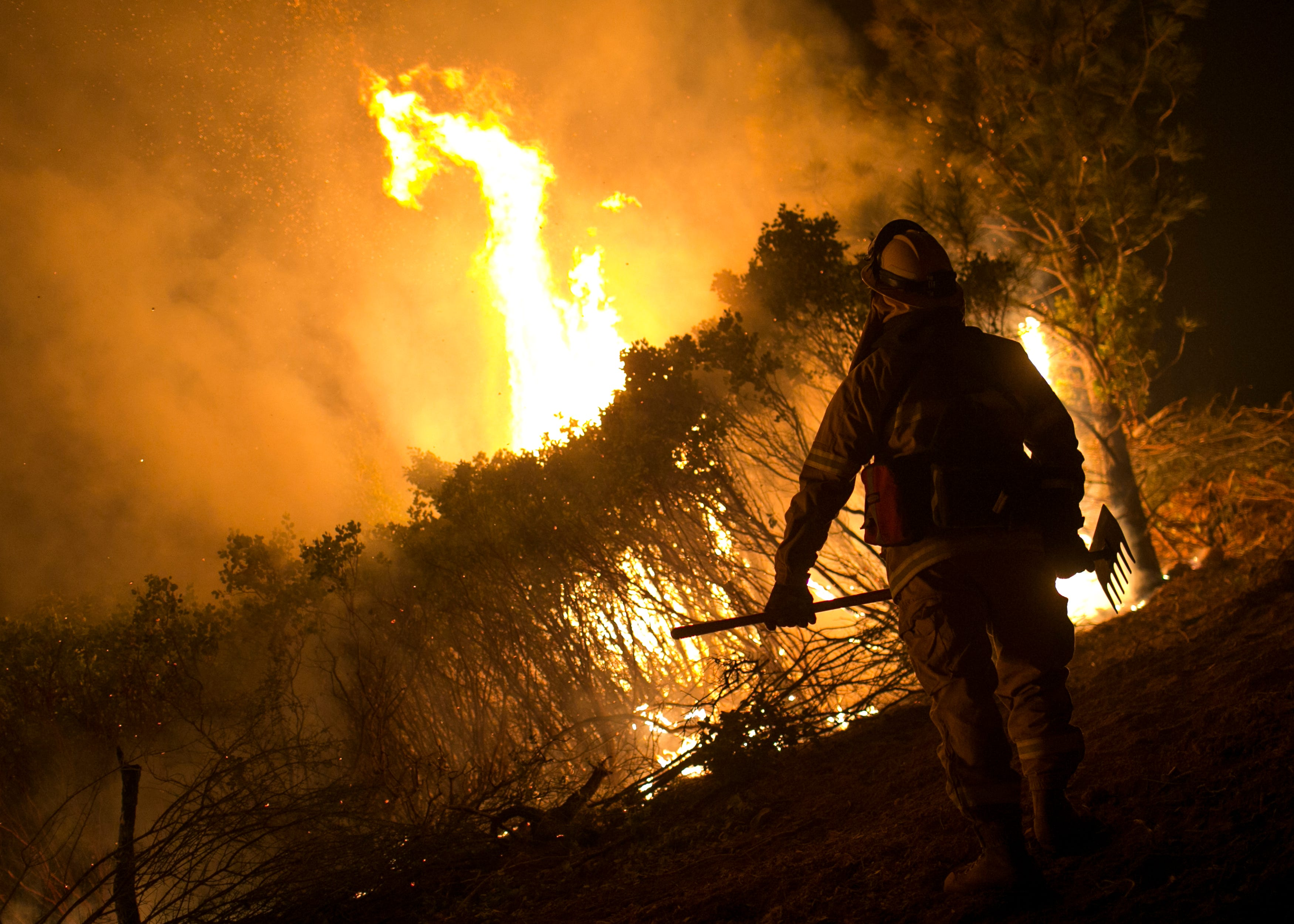 A firefighter stands watch over a controlled burn to fight the Camp Fire in Butte County, California, on Nov. 14. 2018.