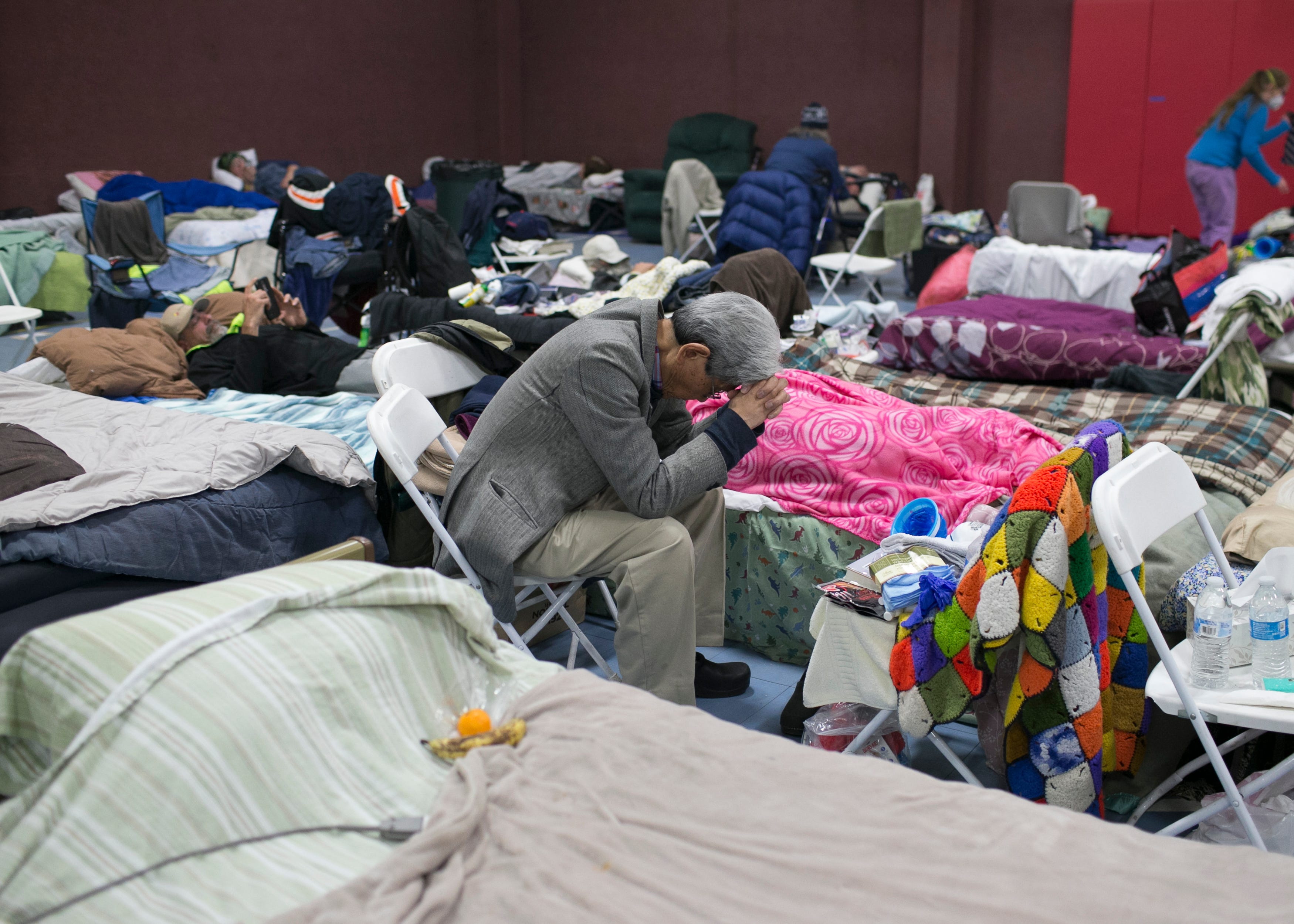 A Paradise evacuee rests with his head in his hands at the East Avenue Church Shelter in Chico on Nov. 15, 2018. The shelter filled less than a week after the fire.