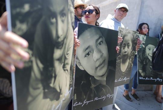 Activistas sostienen en sus manos fotografías de niños que han muerto en su intento de cruzar la frontera entre México y Estados Unidos.