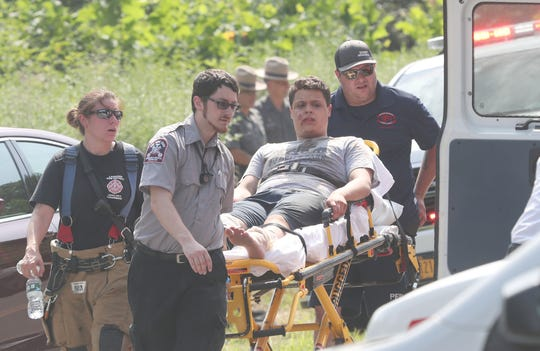 Rescue workers carry an injured person to an awaiting ambulance after a small plane crashed in the woods near Hudson Valley Regional Airport in Wappinger.