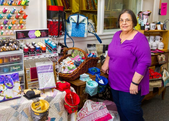 Sylvia Milam, owner of Sylvia's Quilter's Quarters, LLC, stands next to some of the sewing related products at her shop. She will soon be moving to a larger location at 123 West Bridge Street.