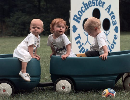 July 1998: Triplets Emma, Sara, and Nathan Ramsey, 16 months old, of Rochester, enjoy playing in a wagon at the Rochester Area Triplets and More picnic at Powder Mills Park.