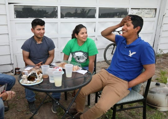 Paola, 28, center, sits with her brothers Gonzalo, 21, left, and Felix, 20, right, on a farm where the brothers work in New York Sunday, June 9, 2019.  The trio were spending a Sunday afternoon together, that they all had off from working on a farm, sharing funny stories and having one last family meal before Paola moves out of the area to work on another farm.