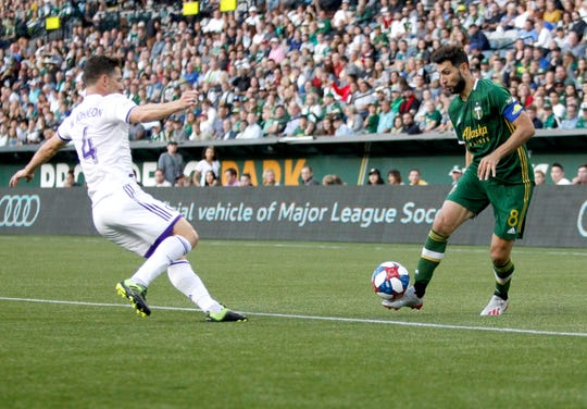 Portland Timbers' Diego Valeri works with the ball in front of Orlando City's Will Johnson during an MLS soccer game Thursday, July 18, 2019, in Portland, Ore.