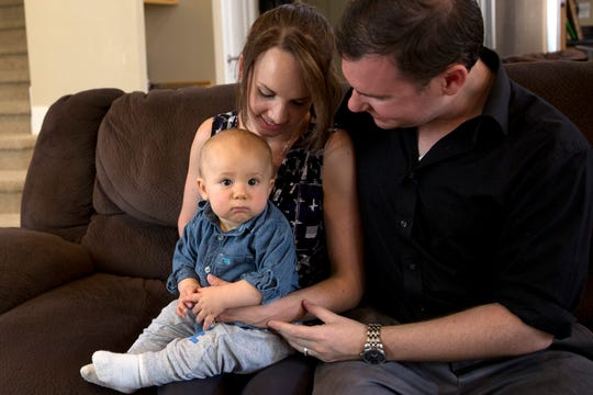 Angela Tipton and Alex Tipton hold their son, Ares, at their home in west Salem on July 17, 2019.