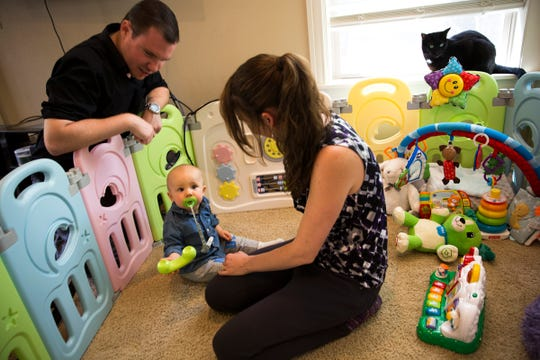 Angela Tipton and Alex Tipton pay with their 11-month-year-old son, Ares, at their home in west Salem on July 17, 2019.