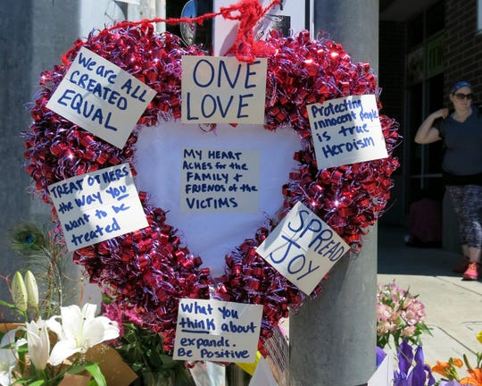 A heart-shaped wreath covered with positive messages hangs on a traffic light pole at a memorial for two bystanders who were stabbed to death Friday, while trying to stop a man who was yelling anti-Muslim slurs and acting aggressively toward two young women, including one wearing a Muslim head covering, on a light-trail train in Portland, Ore, May 27, 2017.