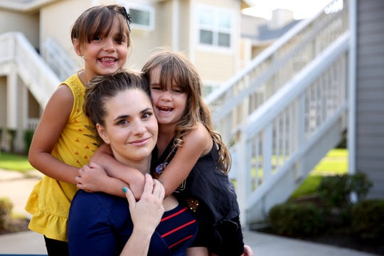 Mariah Dietz with her daughters, Lauren, 6, and Juliette, 5, outside their apartment complex in Salem on July 18, 2019. Dietz, a single mom, was fired after taking too much time off work when her daughters got sick.