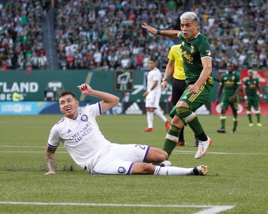 Portland Timbers' Brian Fernandez attempts a shot on goal, next to Orlando City's Kyle Smith during the first half of an MLS soccer game Thursday, July 18, 2019, in Portland, Ore.