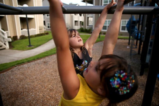 Sisters Juliette Gregory, 5, back, and Lauren Gregory, 6, climb on the monkey bars outside their apartment complex in Salem on July 18, 2019.
