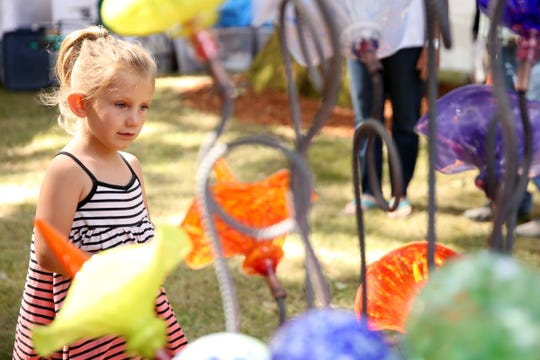 Juniper Lorenzen, 4, of Salem, looks at blown glass art by Andrew Holmberg at the Salem Art Fair and Festival at Bush's Pasture Park in Salem on July 19, 2019. The event continues through Sunday.