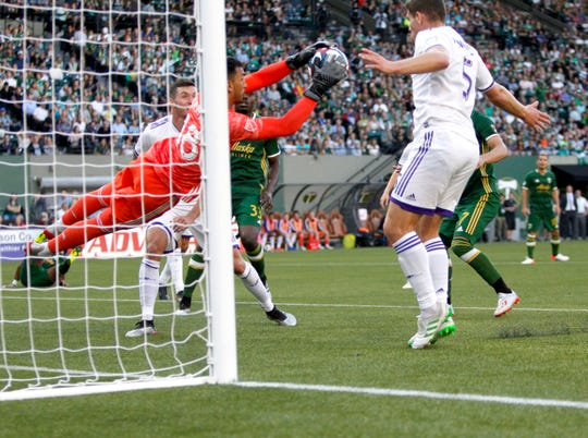 Orlando City keeper Greg Ranjitsingh makes a save next to teammate Dillon Powers, right, during the first half of an MLS soccer game against the Portland Timbers on Thursday, July 18, 2019, in Portland, Ore.