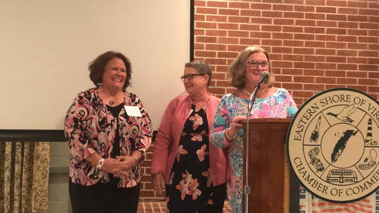 Tammy Holloway, left, accepts the Small Business Person of the Year award from Jeanette Edwards, right, as Patricia Sepety, who nominated Holloway, looks on, during the Eastern Shore of Virginia Chamber of Commerce annual meeting in Accomac, Virginia on Thursday, July 18, 2019.