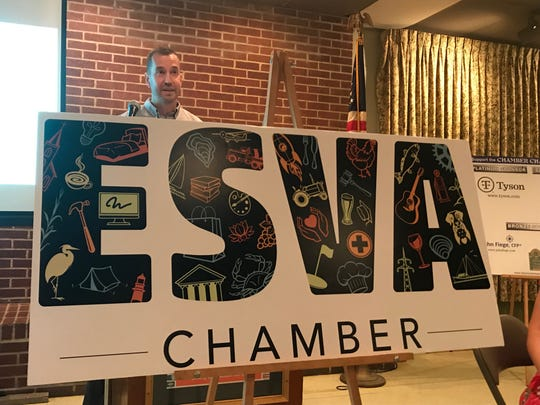 Board member David McCaleb unveils the chamber's new logo during the Eastern Shore of Virginia Chamber of Commerce annual meeting in Accomac, Virginia on Thursday, July 18, 2019.