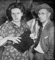 Shirley Hiscox is shown in September 1948 at the time of her arraignment. One of her attorneys, T. G. Owen is to her left.