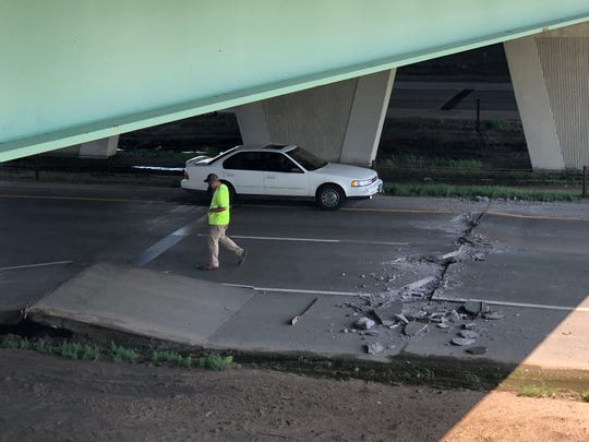Crews work to fix a buckled piece of road on Interstate 229 just south of Western Avenue.