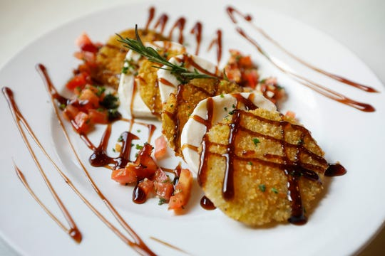 The green tomato caprese consists of parmesan fried tomato slices stacked with buffalo mozzarella, red onions and a balsamic reduction.