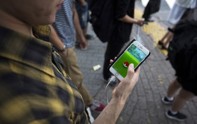 A man plays Pokemon Go on a smartphone as he waits to cross a road in this file photo from 2016.