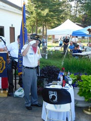 John Pellegrino, the commander of the Wausau American Legion post's honor guard, salutes a display honoring America's prisoners of war and those missing in action. The display was part of the post's 100th anniversary celebration held July 11.
