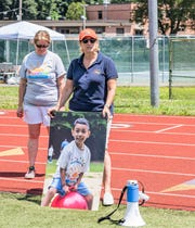 At the July 13 benefit at Clarkstown North High, Sunrise Day Camp bus coordinator Lori Cowen (l) stands with Michelle Warsoff (r), regional director of Sunrise Walks, who displays a photo one of the campers having fun. More than 60 athletes competed in track & field. Funds will go toward Sunrise, a camp in Pearl River for children with cancer and their siblings.