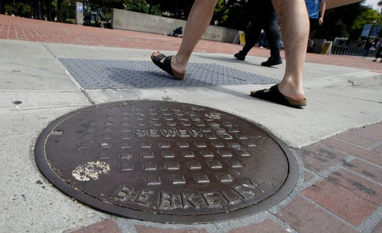 "Pedestrians walk past a manhole cover for a sewer in Berkeley, Calif., Thursday, July 18, 2019. Soon students in Berkeley, California will have to pledge to ""collegiate Greek system residences"" instead of sororities or fraternities and city workers will have to refer to manholes as ""maintenance holes."" Officials in the liberal city this week passed an ordinance to replace some terms with gender-neutral words in the city code. (AP Photo/Jeff Chiu)"