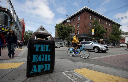 "Traffic and pedestrians cross Telegraph Avenue in Berkeley, Calif., Thursday, July 18, 2019. Soon students in Berkeley, Calif., will have to pledge to ""collegiate Greek system residences"" instead of sororities or fraternities and city workers will have to refer to manholes as ""maintenance holes."" Officials in the liberal city this week passed an ordinance to replace some terms with gender-neutral words in the city code. (AP Photo/Jeff Chiu)"