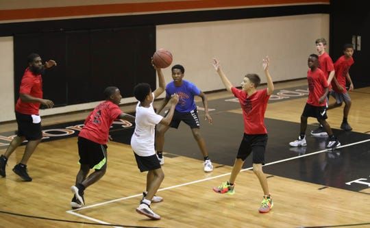 Participants in the Nothing But Net Sports Academy practice basketball in a sweltering gymnasium this week.