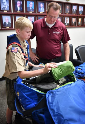 Boy Scout Joseph Brownfield, 14, goes through his duffel bag checking supplies with his father, Greg Brownfield, scout executive for the Northwest Texas Council BSA, in preparation for attending the World Scout Jamboree in West Virginia.