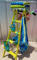 Use the top step of the ladder to hold clean, dry towels. The hooks on the side are for wet, used towels