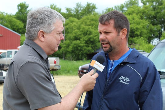 Field day host and dairy farmer Greg Friendshuh talks to a news reporter about the importance of getting farmers and others into the field to learn about innovative conservation practices.