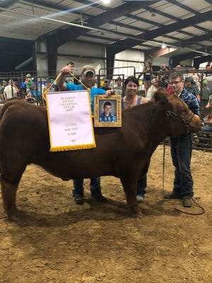 Tristin's father Justin, mother Jessica and brother Chase stand with Rusty, who was awarded Reserve Grand Champion at the Perry County Fair on Thursday night.