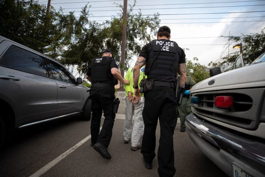 Two U.S. Immigration and Customs Enforcement (ICE) officers walk with a handcuffed man in Escondido, Calif., July 8, 2019