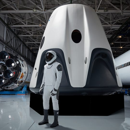 The SpaceX spacesuit that will be worn by astronauts aboard its Crew Dragon spacecraft (in the background) during missions to and from the International Space Station. SpaceX is developing its Crew Dragon spacecraft and Falcon 9 rocket in partnership with NASA's Commercial Crew Program to carry astronauts to and from the space station.
