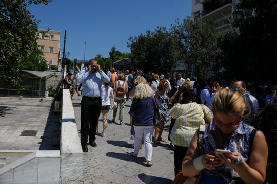 People speak on their phones as they stand outside the building they work in, after a strong earthquake hit near the Greek capital of Athens, Friday, July 19, 2019.