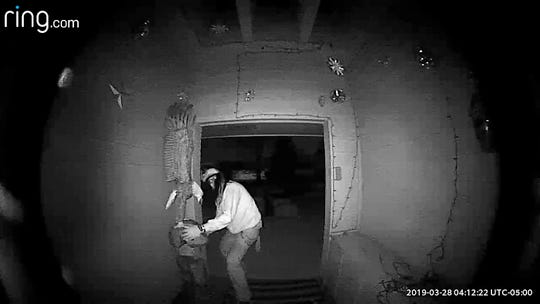 In this Saturday, March 23, 2019, image made from video, a man tries to leave with an bald eagle carving at the Coon Rapids, Minn., home of Larry and Vicki Eklund.