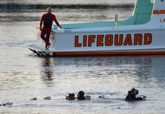 In this April 9, 2015, file photo, divers emerge from the water as debris believed to be from a car floats to the surface where a car went off a pier and into the water in Los Angeles' San Pedro harbor district.
