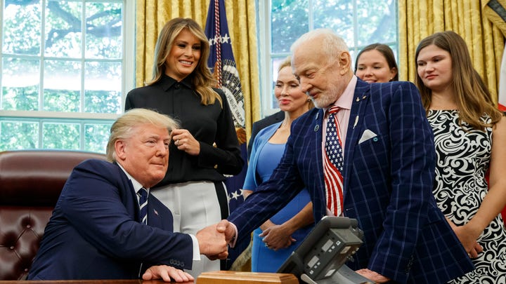 President Donald Trump shakes hands with Apollo 11 astronaut Buzz Aldrin, with first lady Melania Trump, center, during a photo opportunity commemorating the 50th anniversary of the Apollo 11 moon landing, in the Oval Office of the White House, Friday, July 19, 2019, in Washington. (AP Photo/Alex Brandon) ORG XMIT: DCAB129
