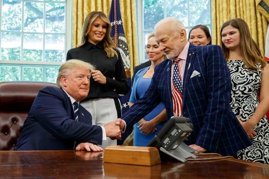 President Donald Trump shakes hands with Apollo 11 astronaut Buzz Aldrin during a photo op commemorating the 50th anniversary of the Apollo 11 moon landing, in the Oval Office of the White House, Friday, July 19, 2019, in Washington, D.C.