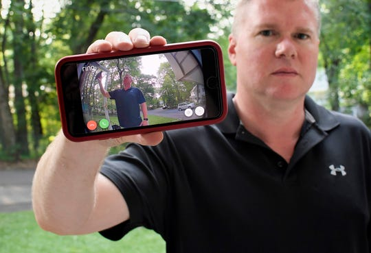 In this Tuesday, July 16, 2019, photo, Ernie Field holds up a live video of himself taken by a Ring doorbell camera at the front door at his home in Wolcott, Conn.