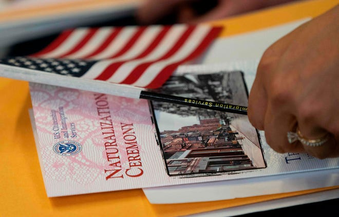 A woman, about to become a US citizen, holds a US flag and naturalization documents during a Naturalization Ceremony at the Tenement Museum June 27, 2019 in New York. The Trump Administration announced Friday that it will make changes to the citizenship test. (Photo by Don Emmert/AFP)