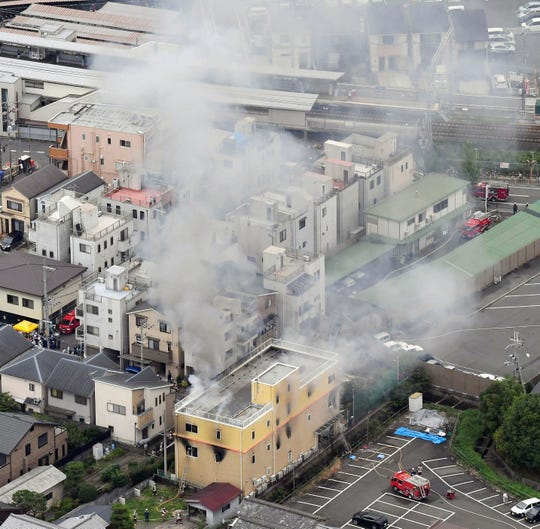 Smoke billows from a Kyoto Animation building, bottom, in Kyoto, western Japan, Thursday, July 18, 2019.