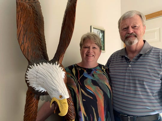 In this Friday, June 28, 2019, photo, Vicki and Larry Eklund pose with their 7-foot-tall bald eagle carving at their home in Coon Rapids, Minn.