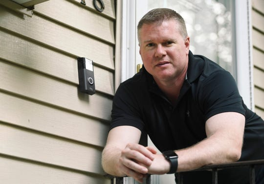In this Tuesday, July 16, 2019, photo, Ernie Field poses for a photograph next to a Ring doorbell camera at his home in Wolcott, Conn.