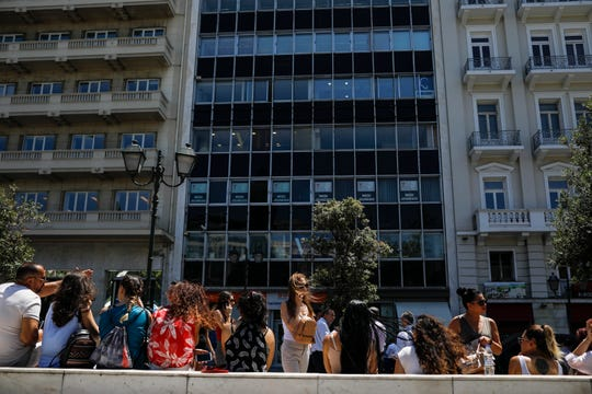 People speak on their phones as they stand outside the building they work in with the Greek Parliament in the background, after a strong earthquake hit near the Greek capital of Athens, Friday, July 19, 2019.