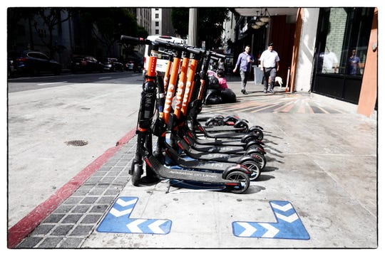 "Scooters parked in the ""Furnishing Zone"" of a city sidewalk in downtown Los Angeles"