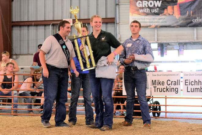 Mariah Cotsamire proudly accepts her Showman of Showmen trophy Friday evening at the Crawford County Fair.