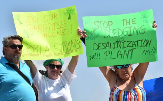 Port Aransas residents hold signs opposing the Port of Corpus Christi's plans for Harbor Island during a protest on Saturday, July 20, 2019.