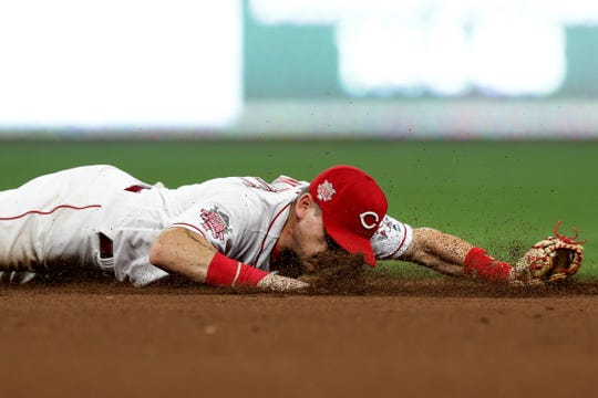 Cincinnati Reds second baseman Scooter Gennett dives for a groundball in the sixth inning against the St. Louis Cardinals in their MLB baseball game on Friday, July 19, 2019, at Great American Ball Park in Cincinnati.